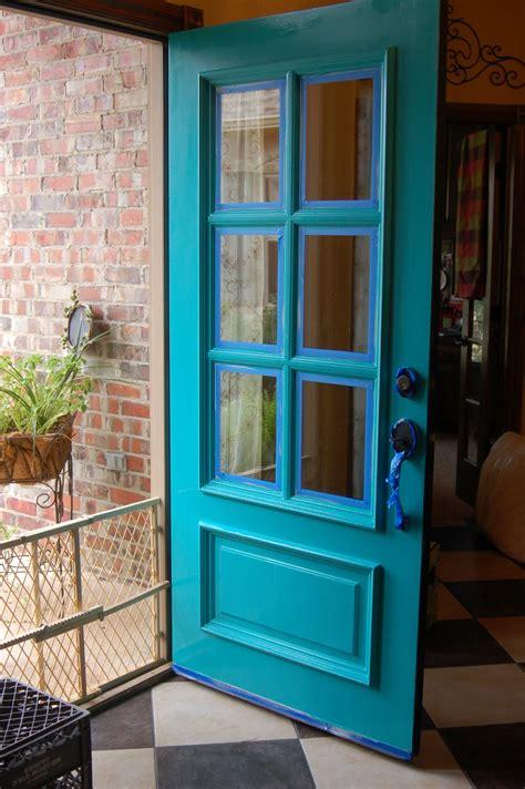 turquoise front door beyond the screen door
