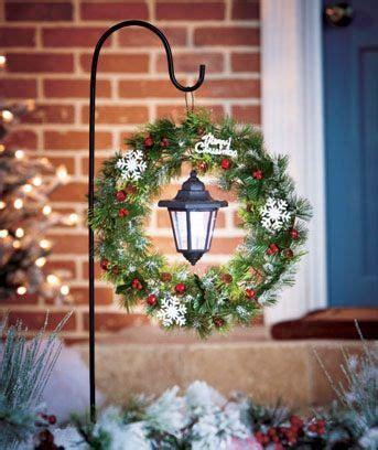 hang a christmas wreath and a solar lantern on a shepherd