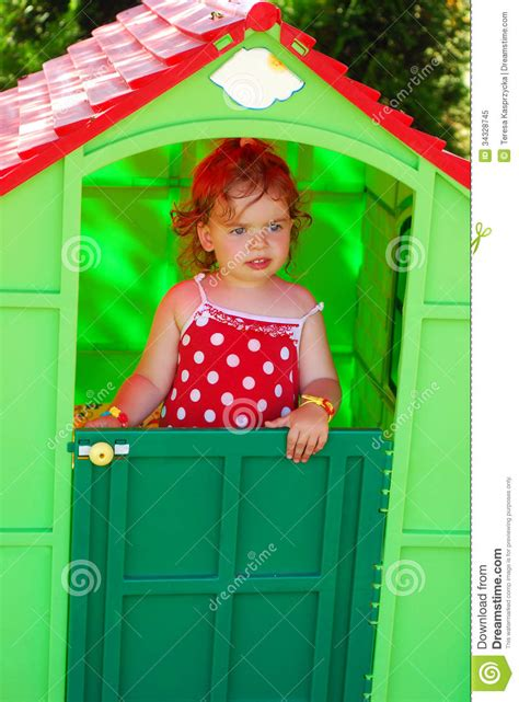 little girl house little girl playing in toy house in the garden royalty free stock photo image 34328745