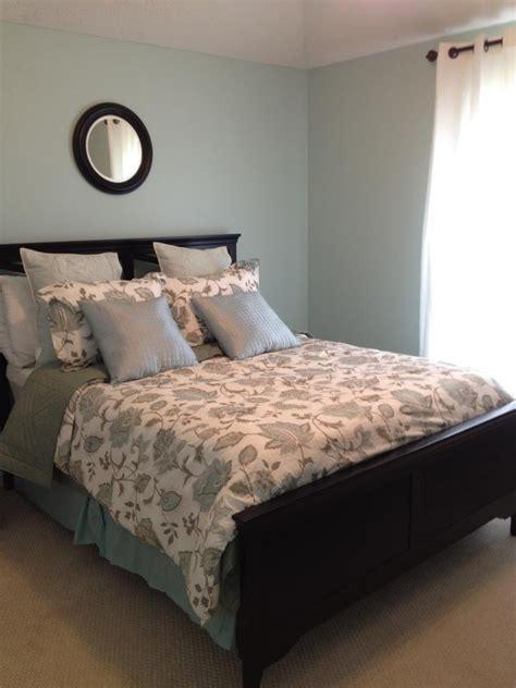 master bedroom blue black circular mirror black bed