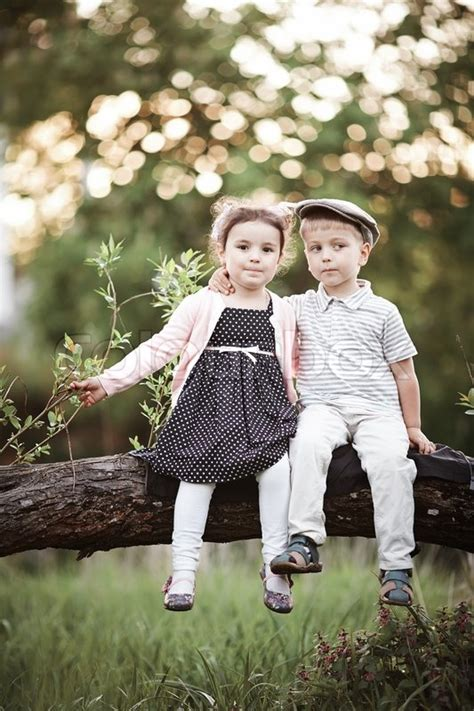 wallpaper of girl and boy together little cute boy and girl sitting on tree stock photo