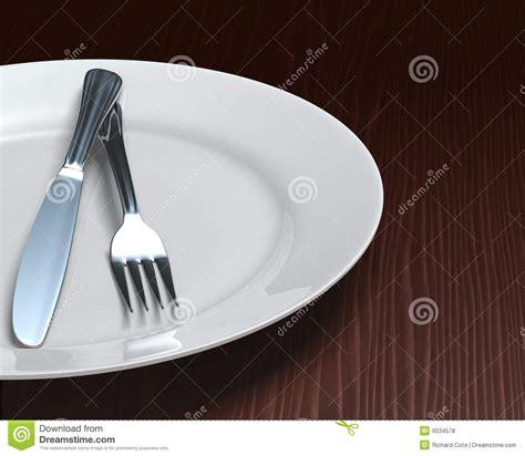 Clean Plate & Cutlery On Dark Woodgrain Table Royalty Free