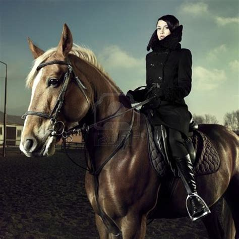 in esteem of the elegant horse equestrian inspired elegant woman in a black coat riding on a brown horse