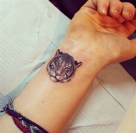 small and nice tiger face tattoo on wrist for stylish
