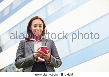 businesswoman outdoors, using smartphone, smiling, tattoos