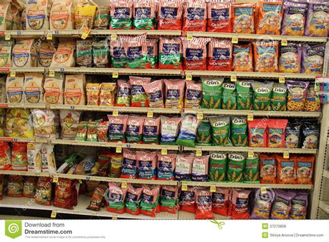 Shelf Of Potato Chips by Crisps Varieties And Potato Chips On A Store Shelf