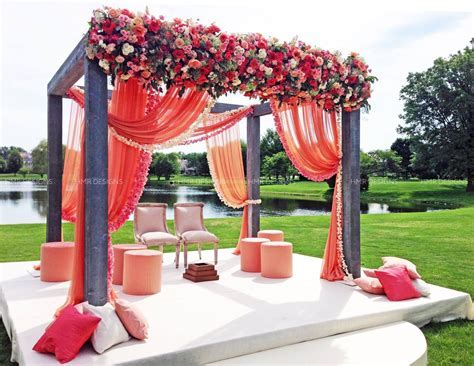 A steel framed canopy or mandap is draped with peach, pink