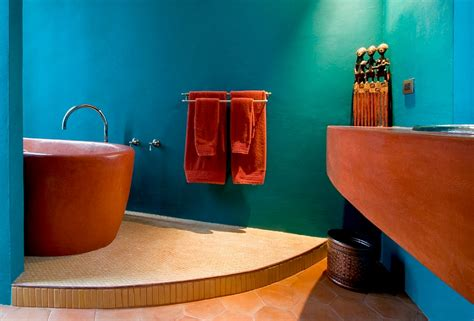 orange bathtub bathtub in bright orange set against a turquoise backdrop