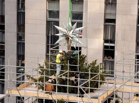 the star is placed on top of the rockefeller christmas