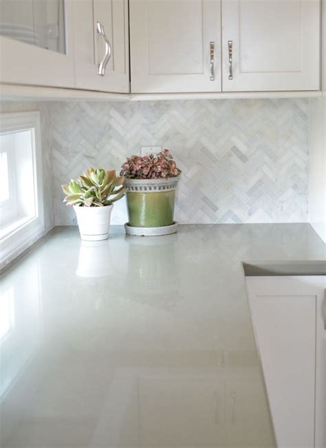 white cabinets with marble herringbone backsplash and sage green quartz countertops backsplash