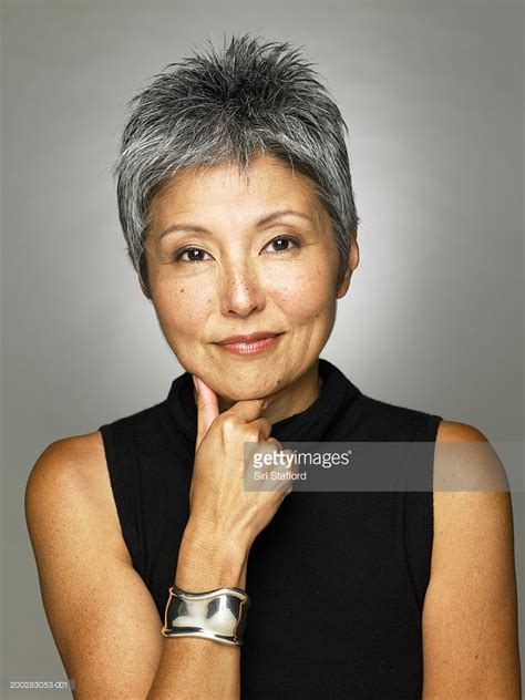 50 year asian women mature woman wearing black top portrait stock photo