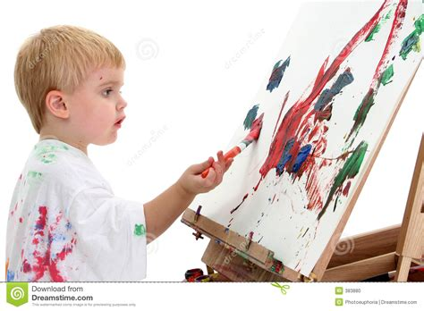 painting boy caucasian toddler boy painting at easel stock photo