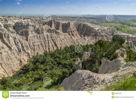 rugged badlands with pine filled valley stock photo