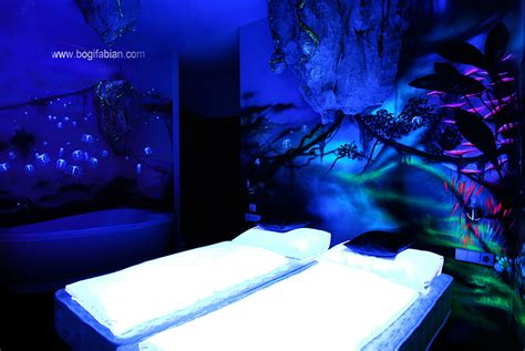artist paints rooms with murals that glow blacklight