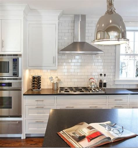 small white kitchen with steel hood stainless steel kitchen range hood ovens tile cupboards