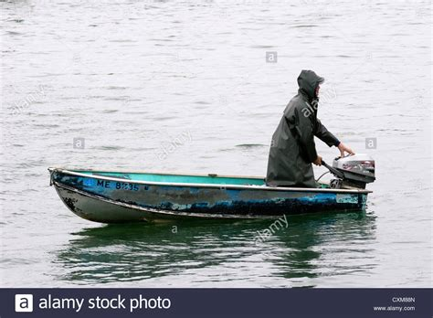 small boat with motor man in a raincoat steering a small motor boat stock photo