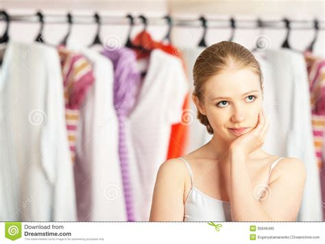 woman chooses clothes   wardrobe closet  home stock