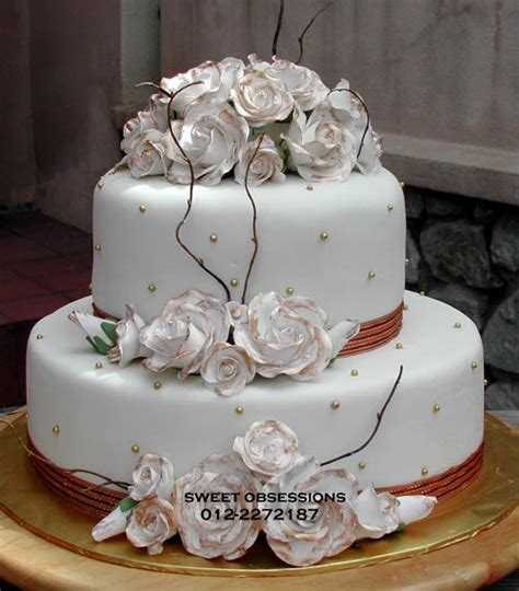 two tier gold and white shabby chic style wedding cake decorated with small gold balls dried