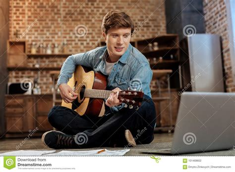 tutorial guitar the man who can t be moved charming man watching playing guitar tutorial stock photo