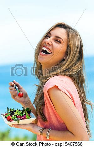 laughing girl eating fresh salad outdoors. stock image