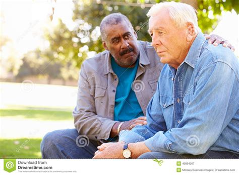 how to comfort a guy man comforting unhappy senior friend outdoors stock photo