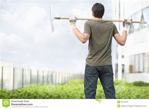 mens haircuts garden city young man holding a rake on his shoulders and looking at