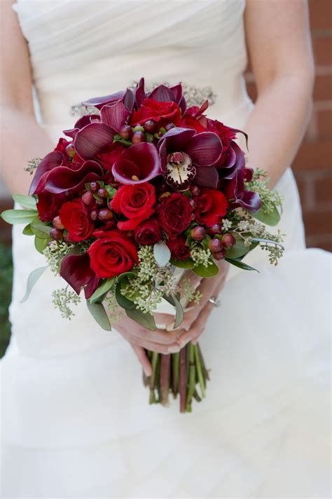 burgundy cymbidium orchid blooms roses and calla lilies arranged beautifully in this bridal