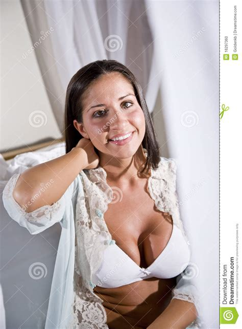 young hispanic woman sitting on white canopy bed stock
