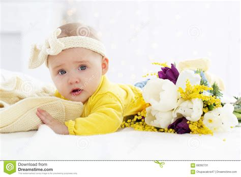 girl lying bed with flowers baby girl in bed with spring flowers stock photo image