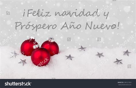 spanish christmas card  red christmas tree balls  text merry christmas   happy