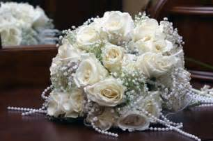 Pictured bridal bouquet with pearl studded ivory roses and a short