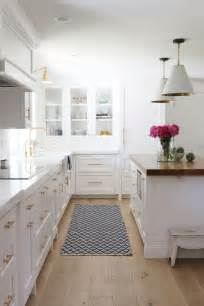 classic white kitchen remodel with wood countertop island and brass counter stools image for