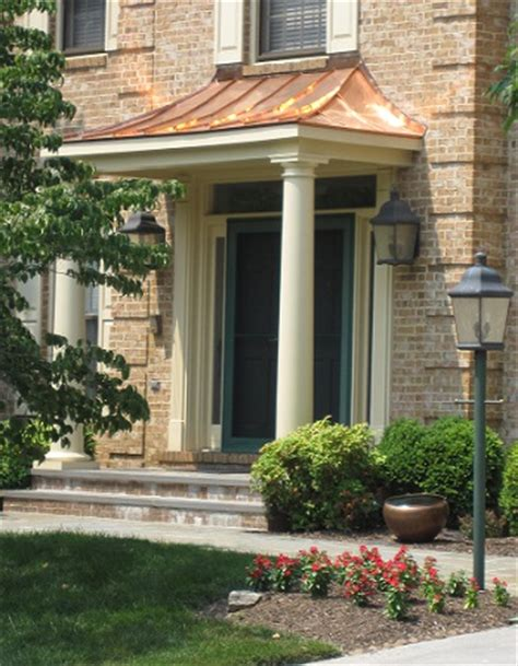 copper portico with tapered columns and patio