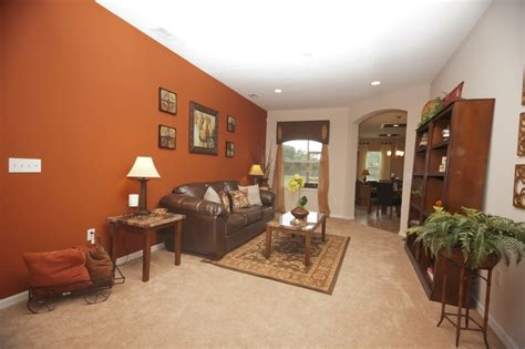 burnt orange accent wall perfectly pairs with the neutral furnishings and flooring highland