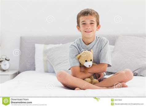 sitting in bed smiling little boy sitting on bed holding his teddy bear