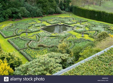 view over formal hedged garden with small pond lawn grass