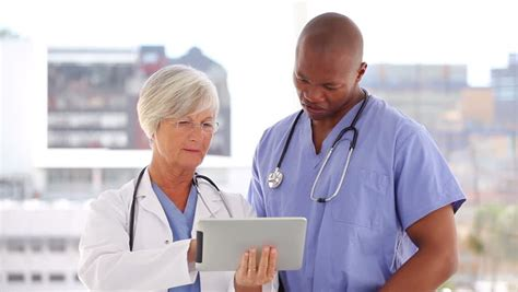 doctor and nurse happy doctor and nurse looking at a tablet pc in a bright