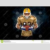 American football player posing in front of dark background.