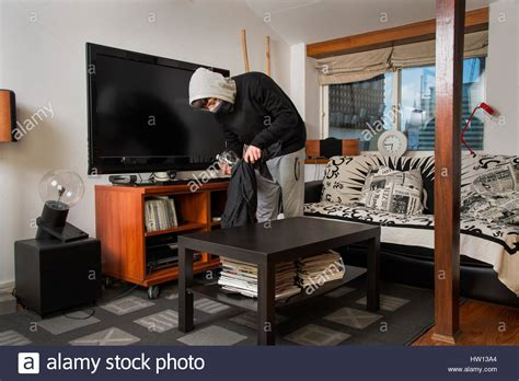 robbing a house burglar robbing a house burglar stealing stuff in a living room stock photo royalty