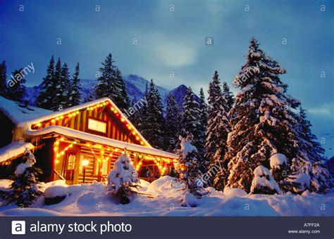 cabin in the snow with christmas lights at night and snow