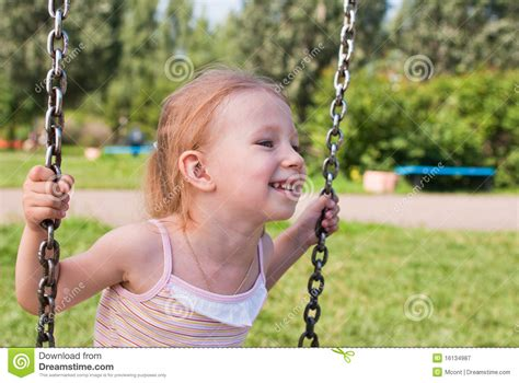 girl swinging on swing little girl swinging on a swing smiling royalty free