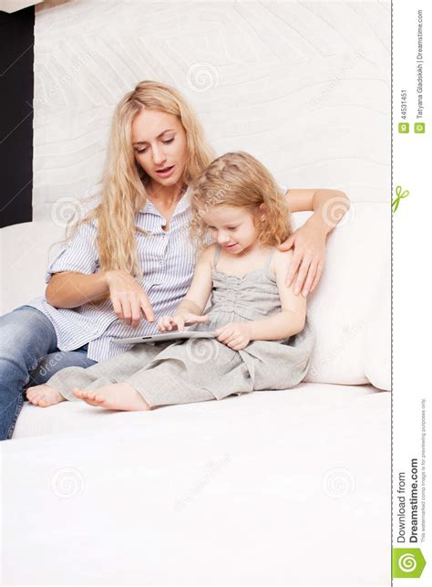 mom on sofa mother and daughter wiht tablet at sofa stock photo