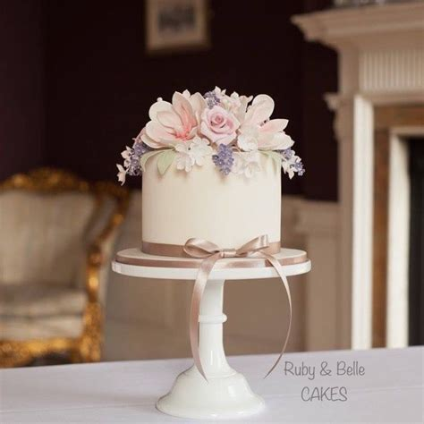 Pretty single tier wedding cake featuring spring flowers