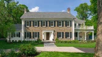 traditional new england colonial house with woodlands