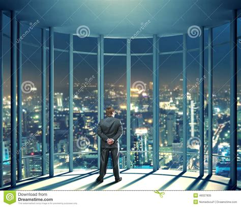 High Rise Building Floor Plan by Night View Of Buildings And Man From Glass Window Stock