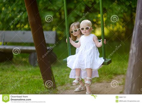 swing swing swing on a summer day two sisters having fun on a swing on summer day stock