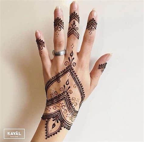 corak henna merah cantik terukir atas tangan