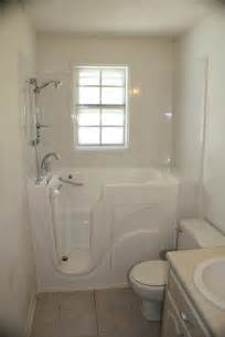 modern white corner walk in tub with outward door which