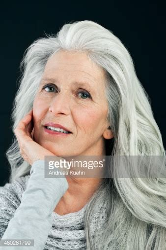 photos of seventy year old silver hair ladies mature woman with long gray hair portrait stock photo