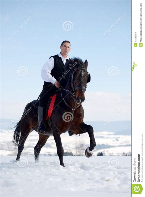 black riding young man riding horse outdoor in winter stock image